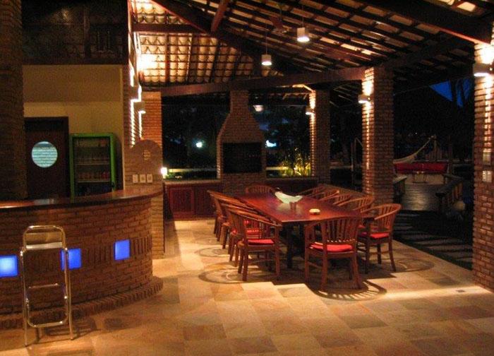 Photo de nuit de la salle à manger avec le bar lumineux à gauche.